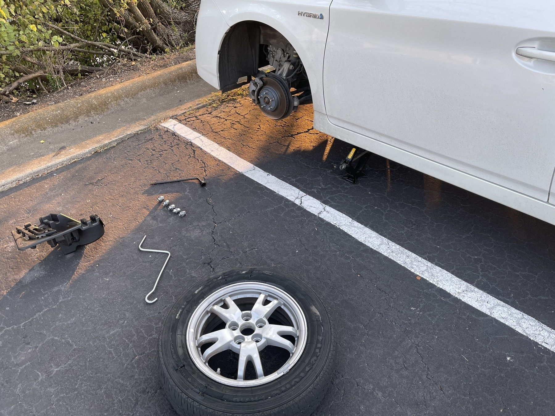 The front left side of a white Toyota Prius is shown on a jack with its tire removed. The tire is down on the next parking spot over, showing damage. Various tools are next to the tire on the ground.